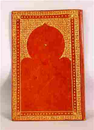 AN ISLAMIC LEATHER BOUND AND GILT QURAN COVER -