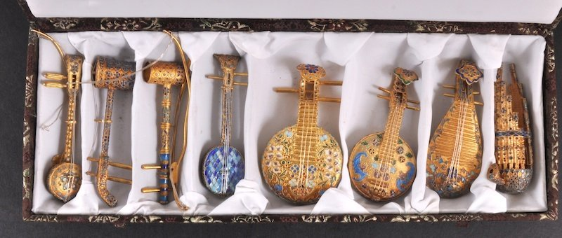 1: A COLLECTION OF EIGHT GILDED AND ENAMEL SMALL MUSICA