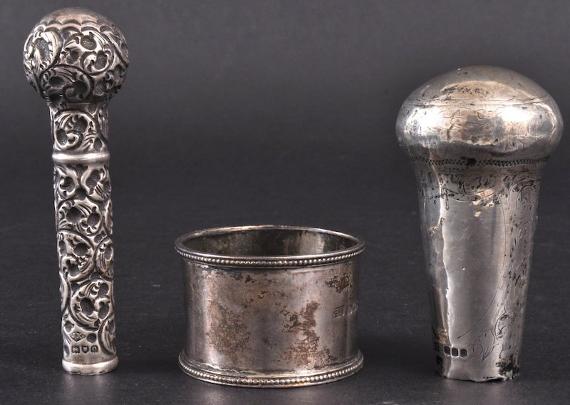 18: TWO SILVER PARASOL HANDLES and a SERVIETTE RING (3)