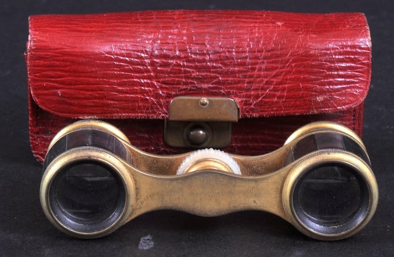 24: A SMALL PAIR OF OPERA GLASSES in a leather case.