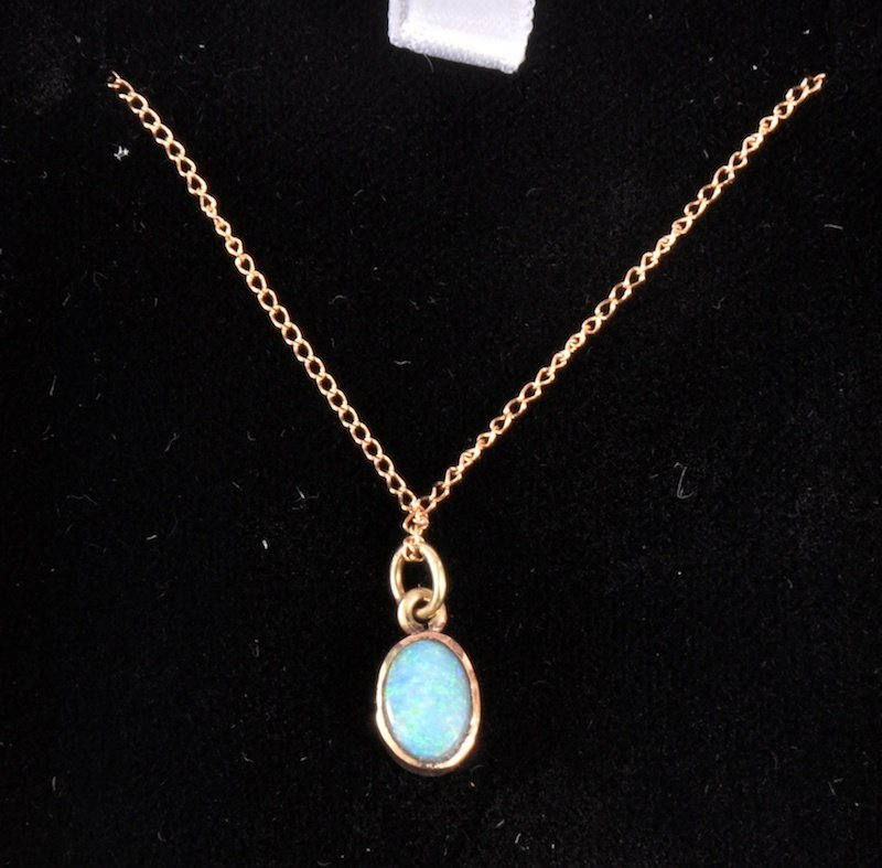 200: A GOLD OVAL OPAL PENDANT on a fine gold chain.