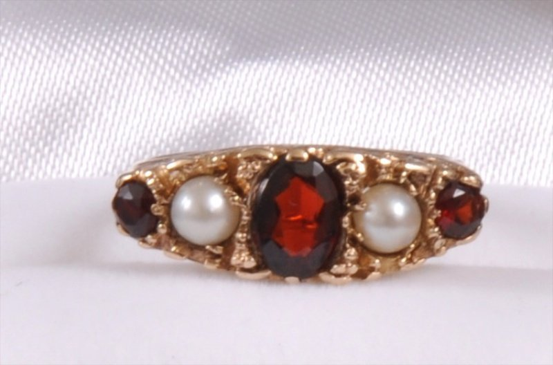 202: A 9CT GOLD GARNET AND PEARL DRESS RING in carved m