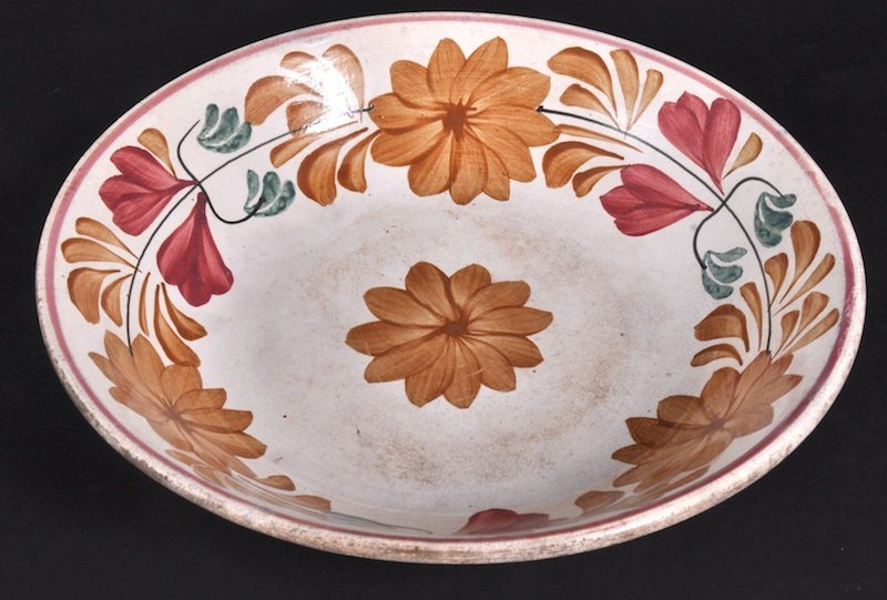 853: A COLOMBO CIRCULAR POTTERY DISH decorated with flo