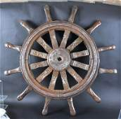 1195  A LARGE BRASS MOUNTED WOODEN SHIPS WHEEL 38ins