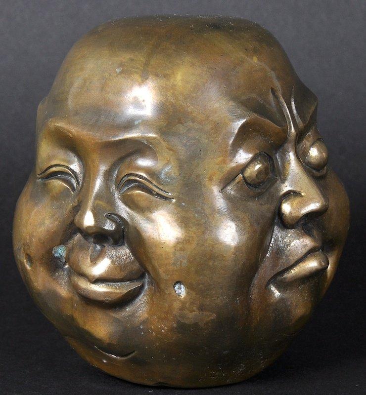 A BRONZE FOUR FACED BUDDHA HEAD.