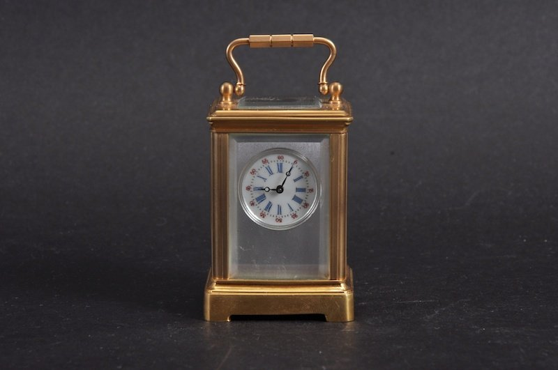 A MINIATURE BRITISH CARRIAGE CLOCK with silvered dial.