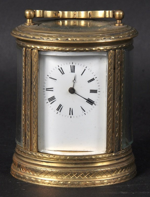 A SMALL OVAL ENGMAN BRASS CARRIAGE CLOCK with carrying