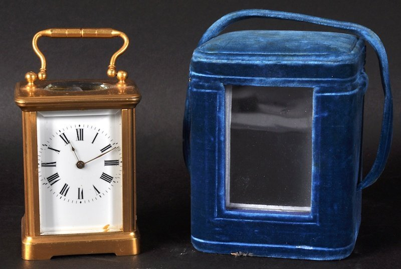 A SMALL OVAL ENGRAVED BRASS CARRIAGE CLOCK with