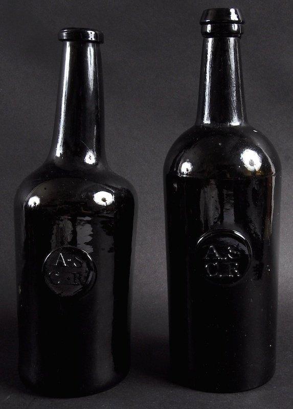A PAIR OF 18TH CENTURY BROWN GLASS BOTTLES.  Circular m