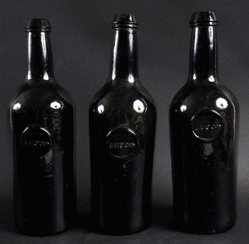 A SET OF THREE 18TH CENTURY BROWN GLASS BOTTLES.  Circu