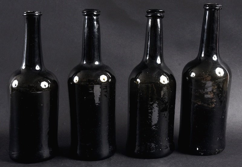 A SET OF FOUR BROWN GLASS BOTTLES.  11ins high.