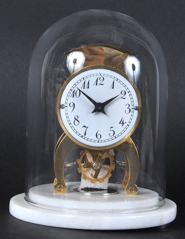 A WEHRLE BRASS CLOCK in a glass dome on a white marble