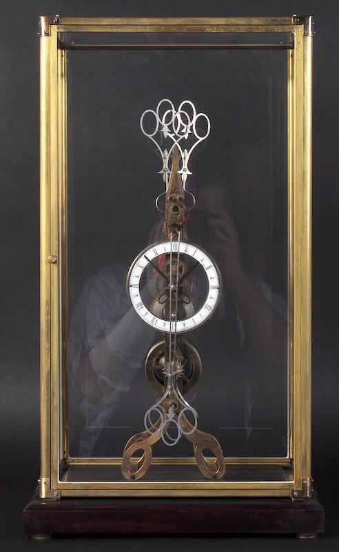 A 'SCISSORS' BRASS SKELETON CLOCK in a glass case. 21
