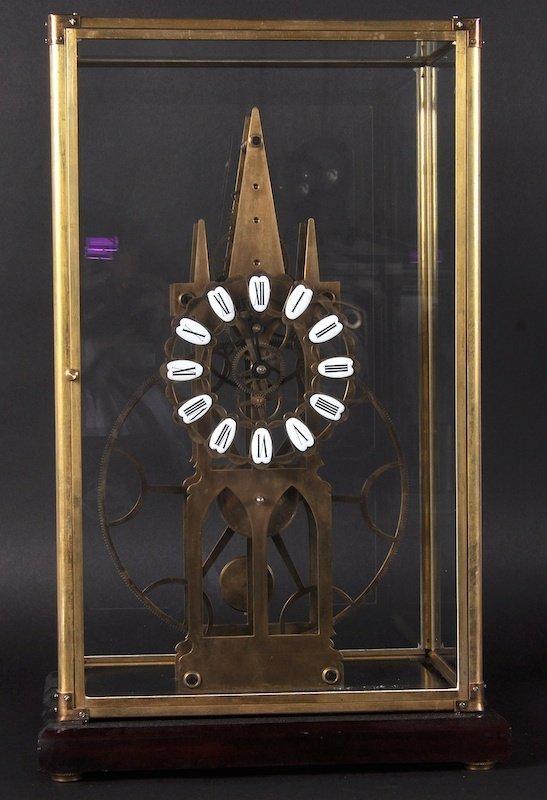 A 'BIG WHEEL' BRASS SKELETON CLOCK in a glass case. 21