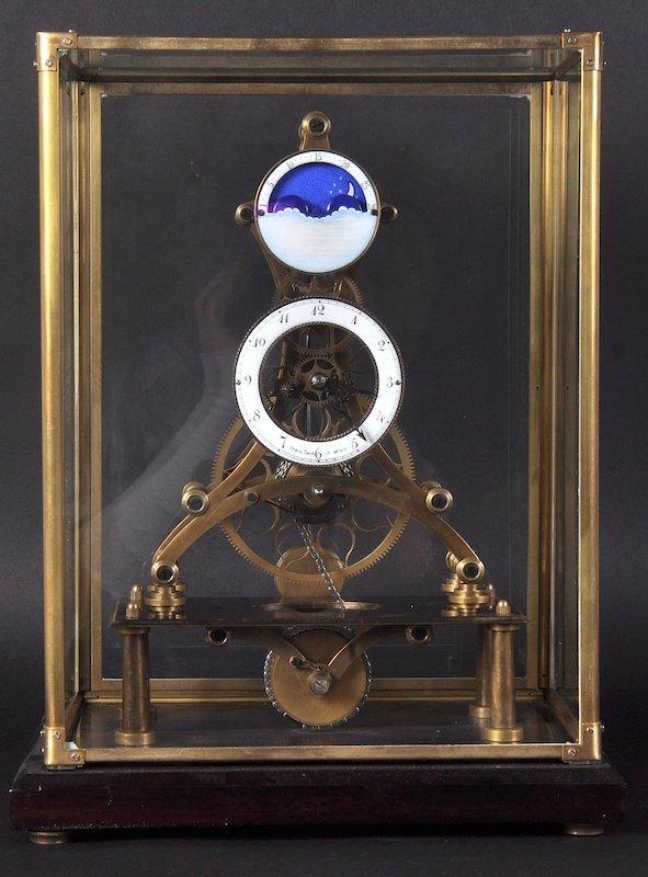 A 'MOON' BRASS SKELETON CLOCK in a glass case. 17