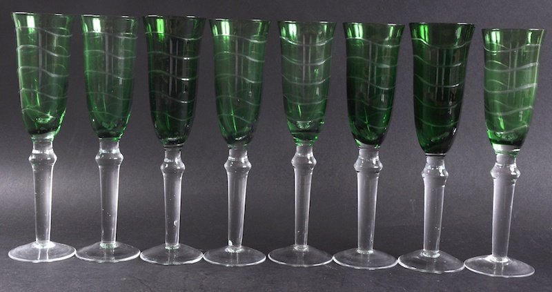 A SET OF EIGHT GREEN TINTED CUT WINE GLASSES.