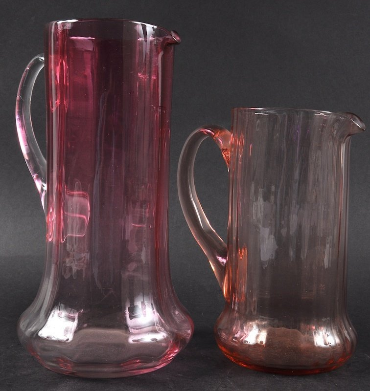 TWO CRANBERRY WATER JUGS.