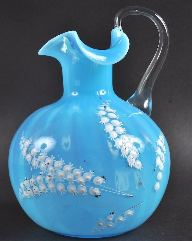 A BLUE GLASS VASELINE JUG painted with lilies of the