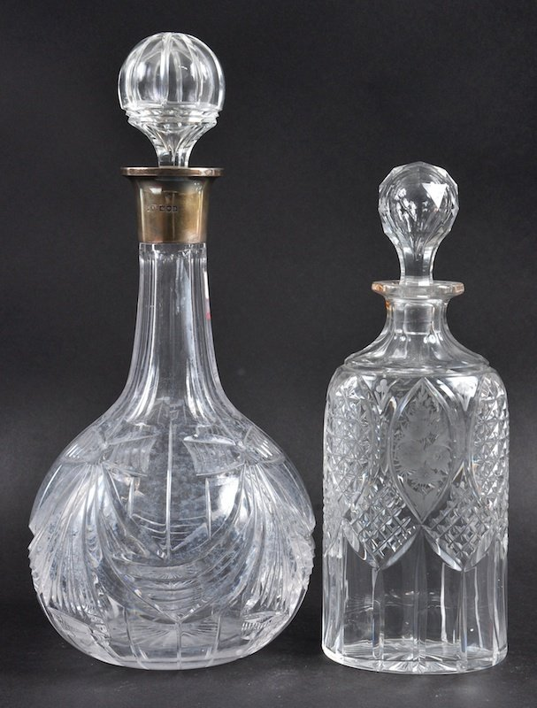A CUT GLASS PORT DECANTER AND STOPPER with silver band