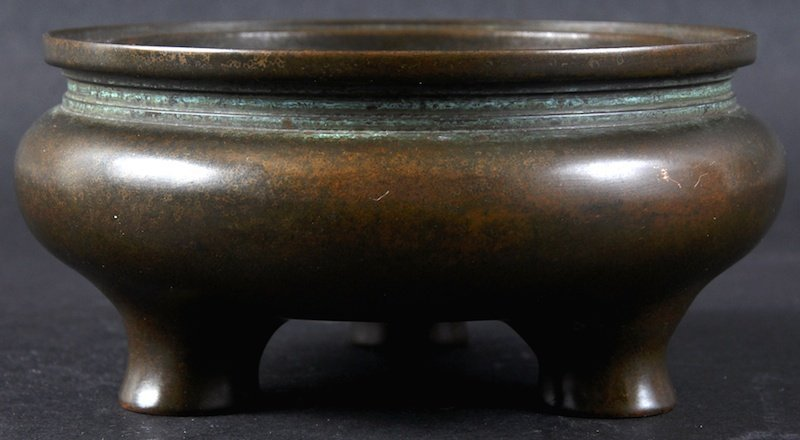 A CHINESE CIRCULAR BRONZE CENSER supported on three