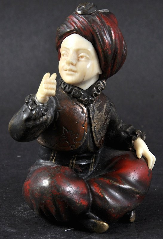 A SMALL BRONZE AND IVORY FIGURE OF A SEATED ARAB BOY,