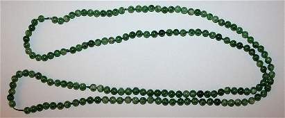 A LONG CHINESE GREEN JADELIKE NECKLACE composed of