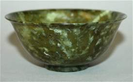 AN EARLY 20TH CENTURY CHINESE MOTTLED GREEN JADE-LIKE