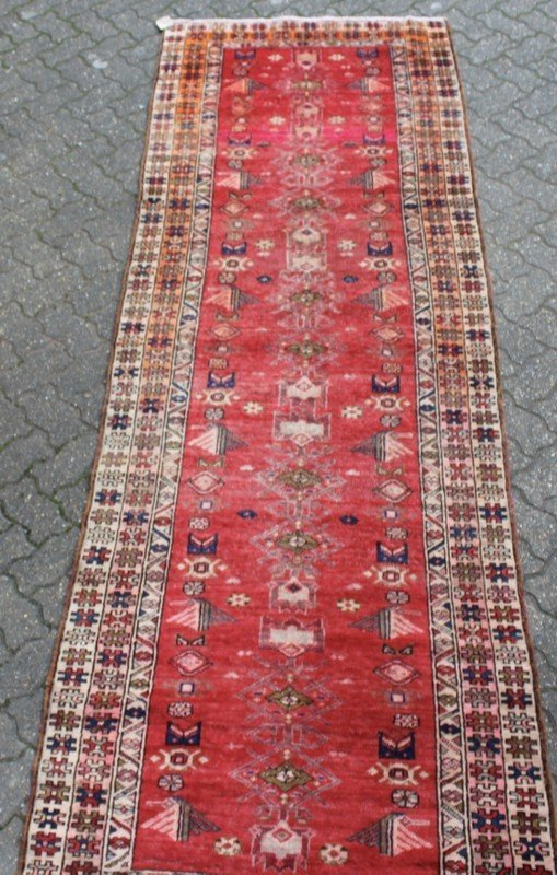 A HAMADAN LONG CARPET, bright red ground within a