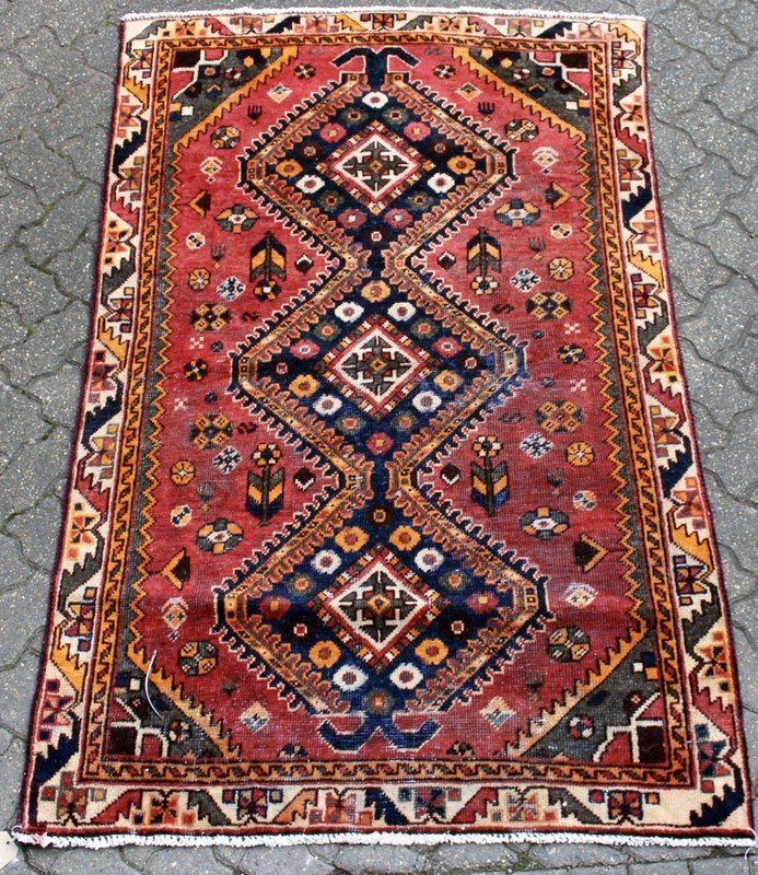 A SMALL SHIRAZ RUG, bright red ground with three