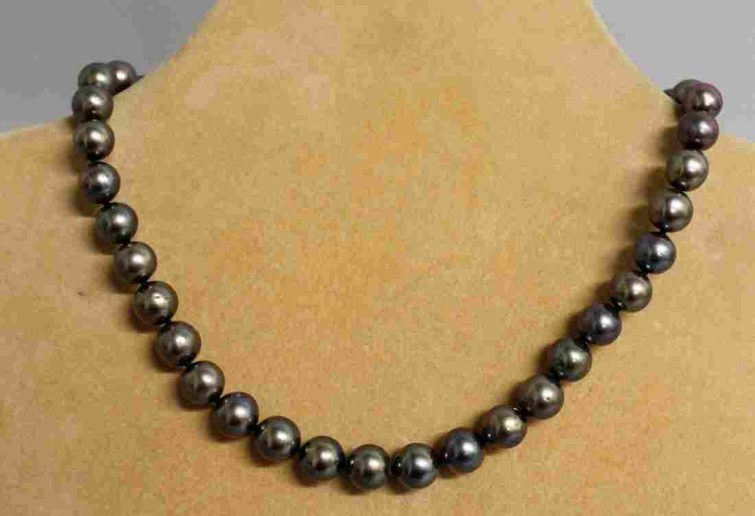 708.  A STRING OF SOUTH SEA BLACK PEARLS with yellow