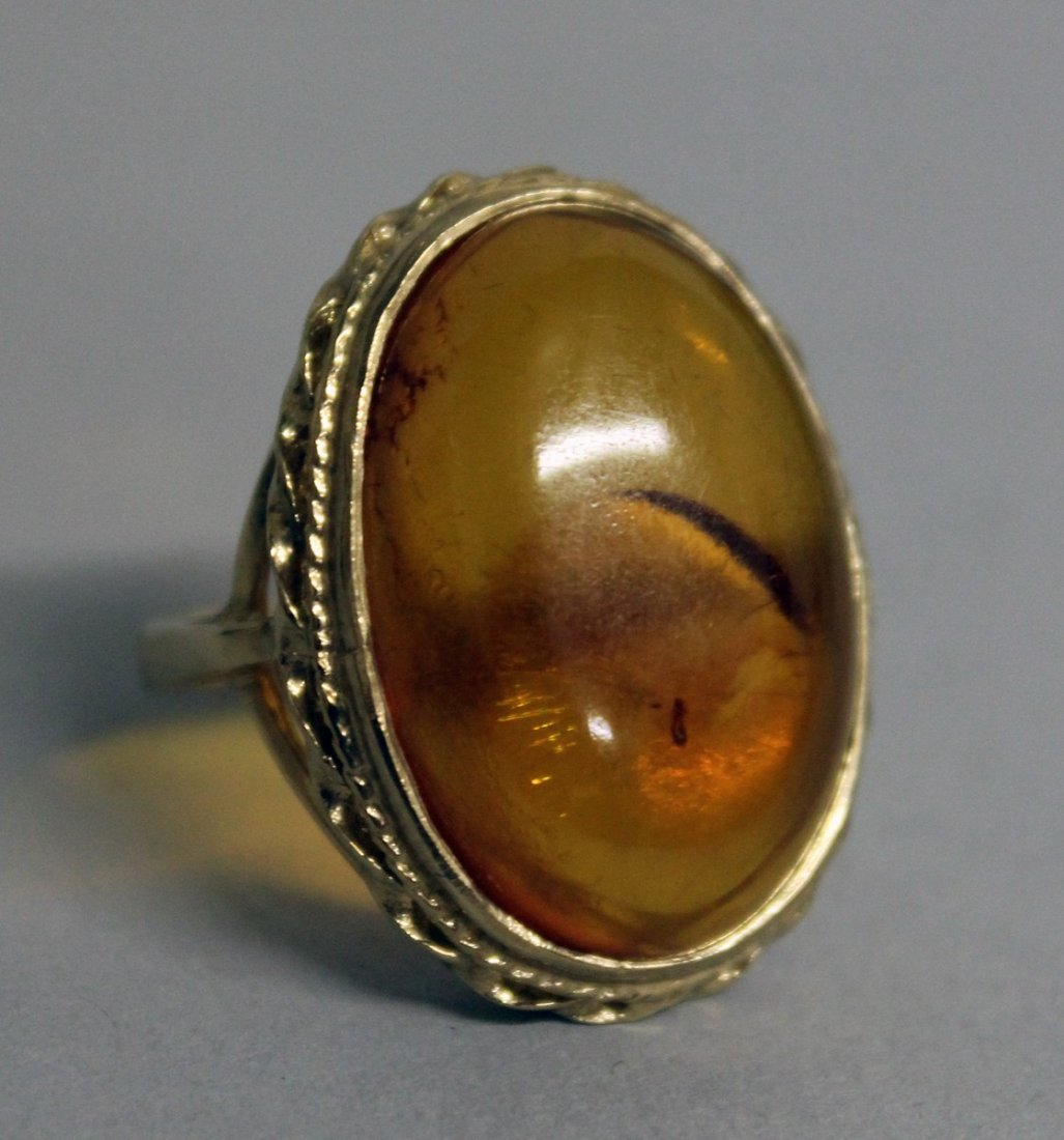 793.  A LARGE 9CT GOLD BALTIC AMBER RING.
