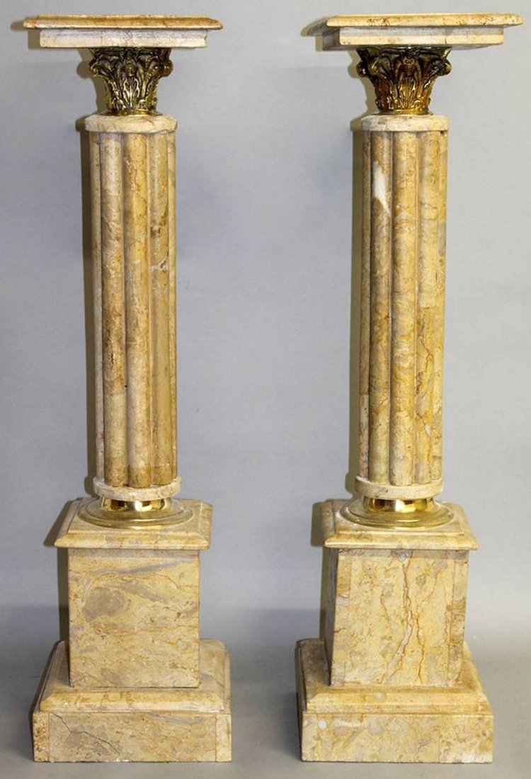 A PAIR OF CREAM MARBLE PEDESTALS with cluster columns