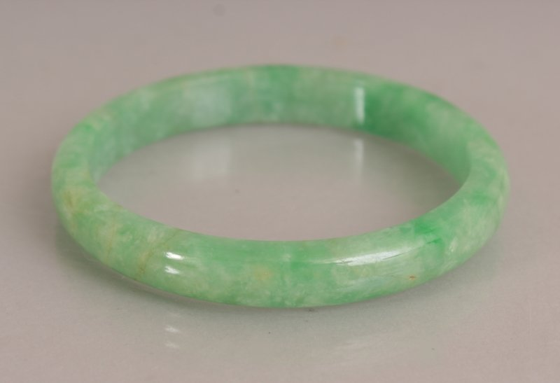 A CHINESE APPLE GREEN JADE BANGLE, with paler - 2
