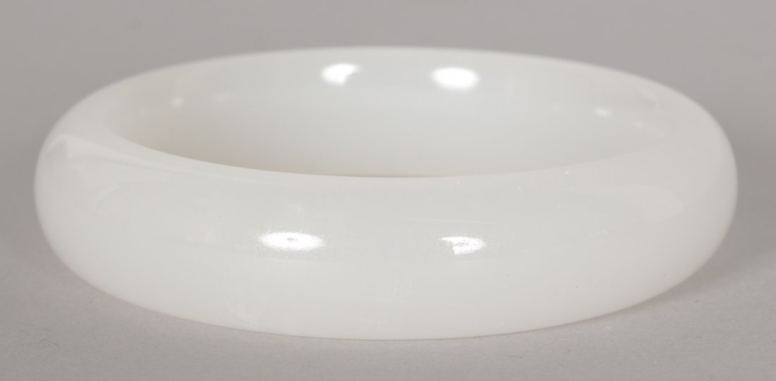 A CHINESE WHITE JADE BANGLE, 2.9in diameter, the inner