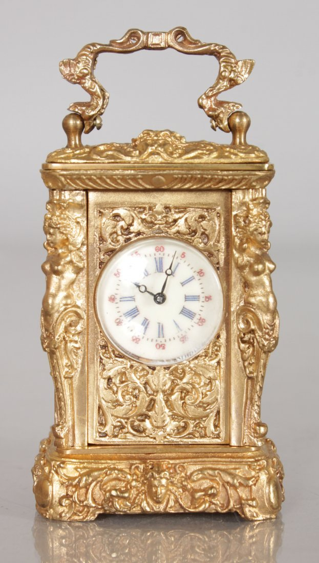 A MINIATURE BRASS CARRIAGE CLOCK with caryatid figures.