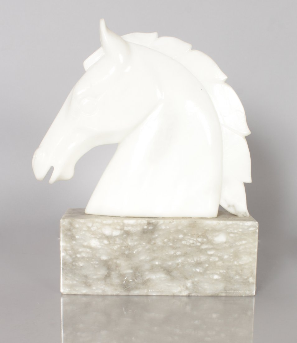 A CARVED WHITE MARBLE HORSES HEAD on a plinth.  11ins