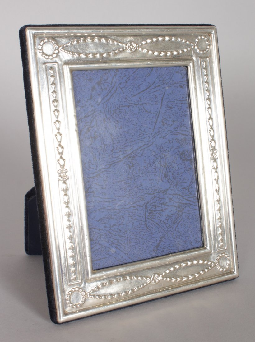 A SILVER UPRIGHT PHOTOGRAPH FRAME decorated with