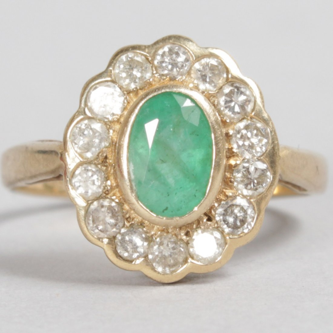 A 9CT YELLOW GOLD, EMERALD AND DIAMOND OVAL CLUSTER