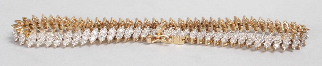 A LOVELY 9CT YELLOW GOLD AND DIAMOND FLEXIBLE BRACELET.