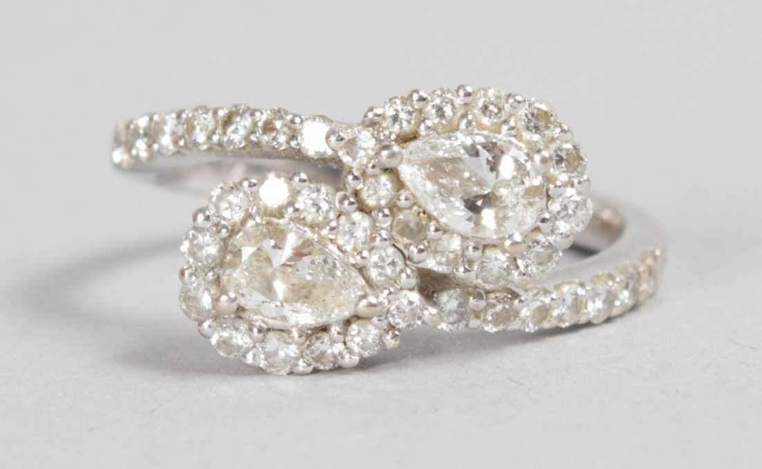 AN 18CT WHITE GOLD DIAMOND TEARDROP CROSSOVER RING.