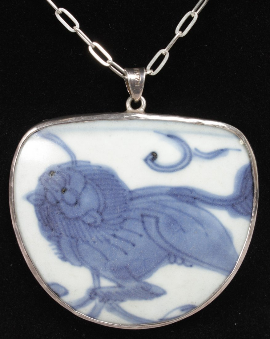A SILVER MOUNTED MING BLUE AND WHITE PENDANT on a