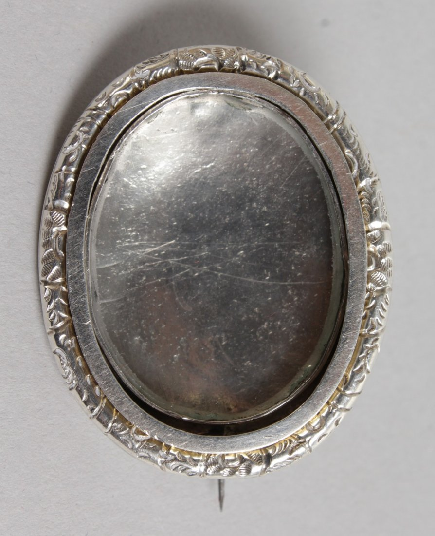 A SILVER OVAL MINIATURE FRAME BROOCH.