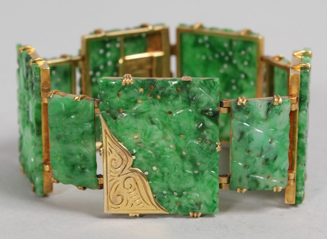 A SUPERB GOLD MOUNTED PIERCED AND CARVED GREEN JADE