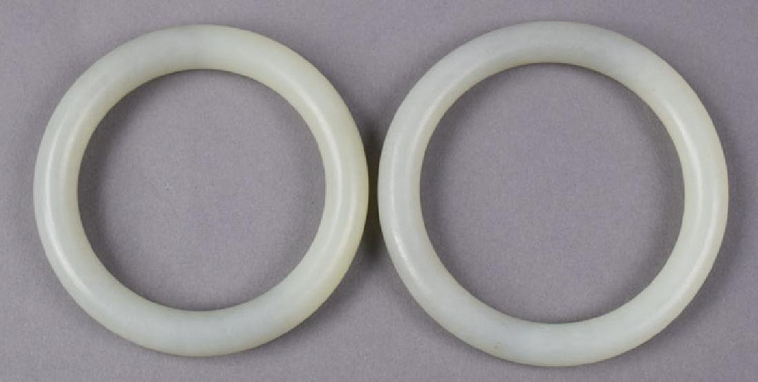 Two Chinese carved white jade bangles