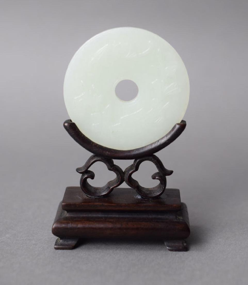 Chinese carved Bi disk raised on a rosewood stand