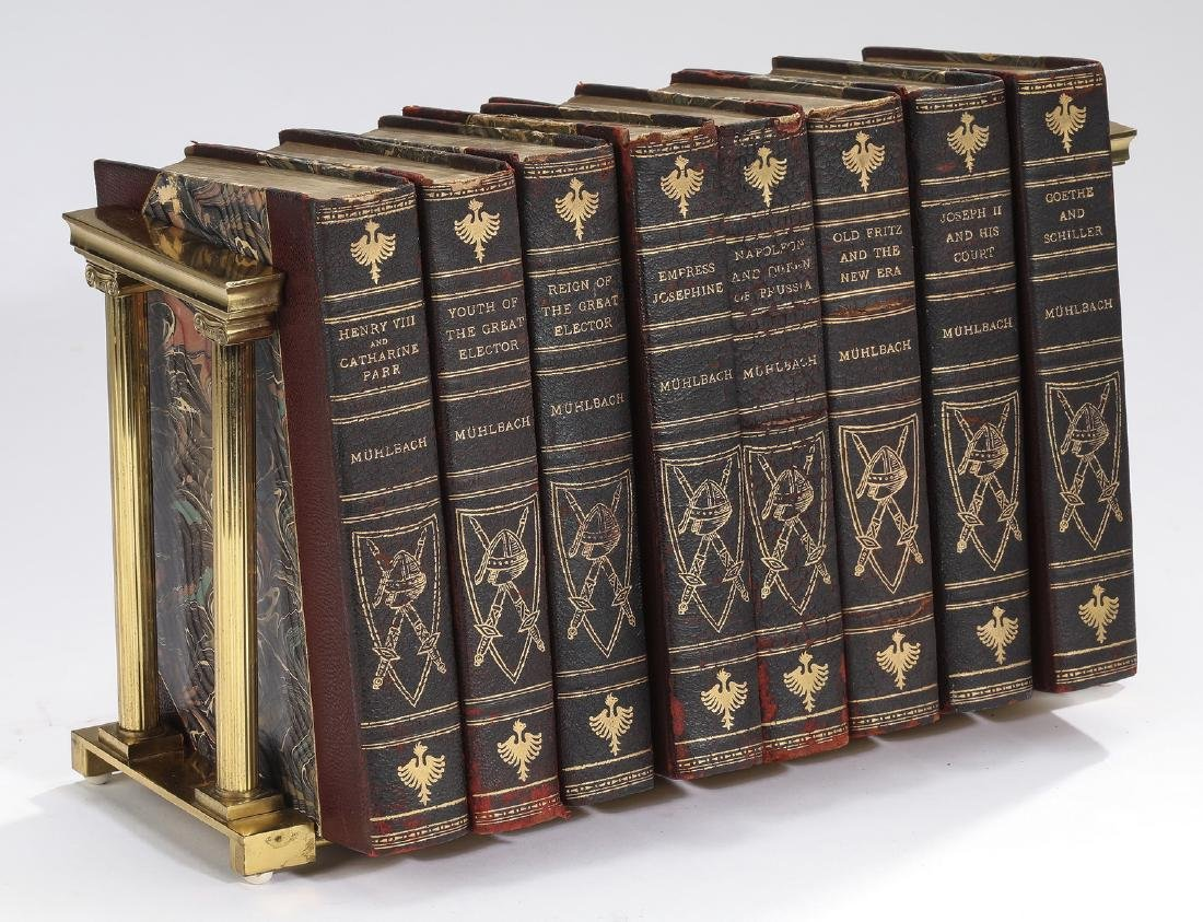 (8) Leather bound novels by Muhlback & brass rack
