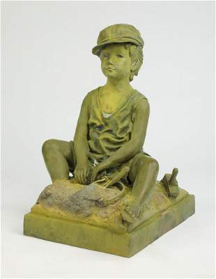 Patinated bronze sculpture of boy playing in the sand