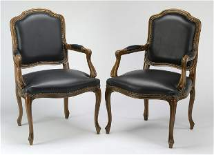 (2) Mahogany armchairs upholstered in black leather