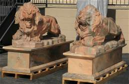 Carved peach marble lions on plinths 81l