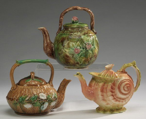 "Group of three majolica teapots, 8""h"